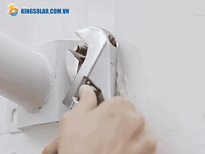 Cố định thanh cán đèn lên tường hoặc cột đèn
